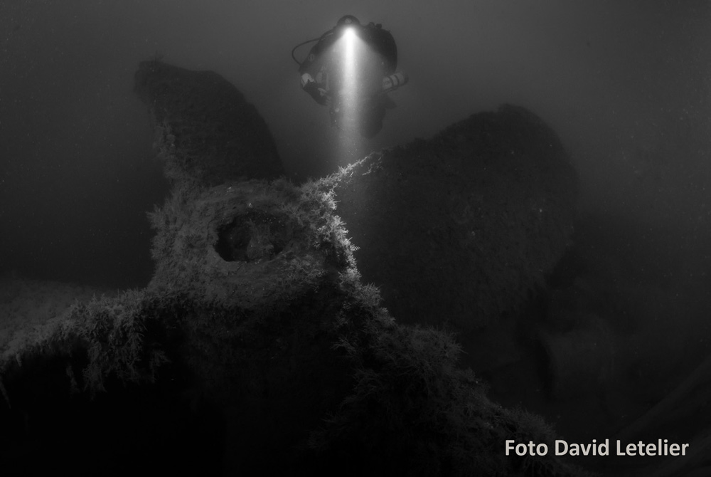 Scuba diver shining light on wreck photographer Davvid Letelier